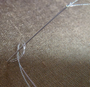 A French knot being worked with the double metallic thread.