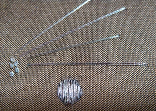 Examples of French knots and satin stitch. The radiating lines have been laid ready to be held down with silk.